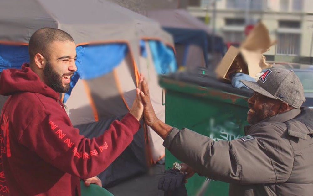 Josh Yazdian (left) high fives a homeless man in Los Angeles. Yazdian has donated thousands of clothing items to the homeless through his company, Yaz Apparel.