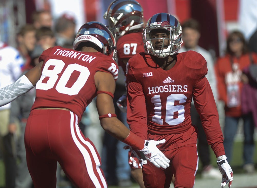 Cornerback Rashard Fant (16) high fives Leon Thornton III (80) before the game against Rutgers Saturday at Memorial Stadium. The Hoosiers lost, 52-55.