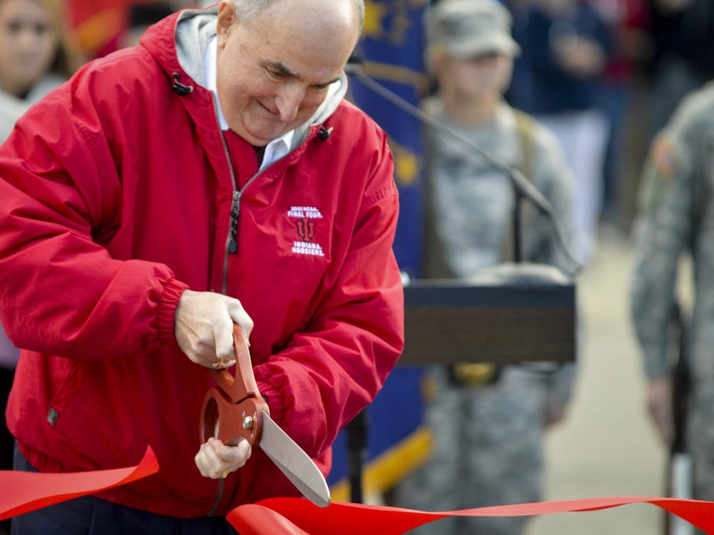 IU President Michael McRobbie cuts a ribbon to make homecoming weekend official during the 2018 homecoming parade evening at Woodlawn Avenue. More than 100 IU facilities were constructed or renovated during McRobbie's tenure, according to the university.