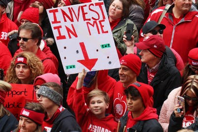 "An Indiana student holds a sign that reads ""invest in me"" Nov. 19 at the Indiana Statehouse in Indianapolis."