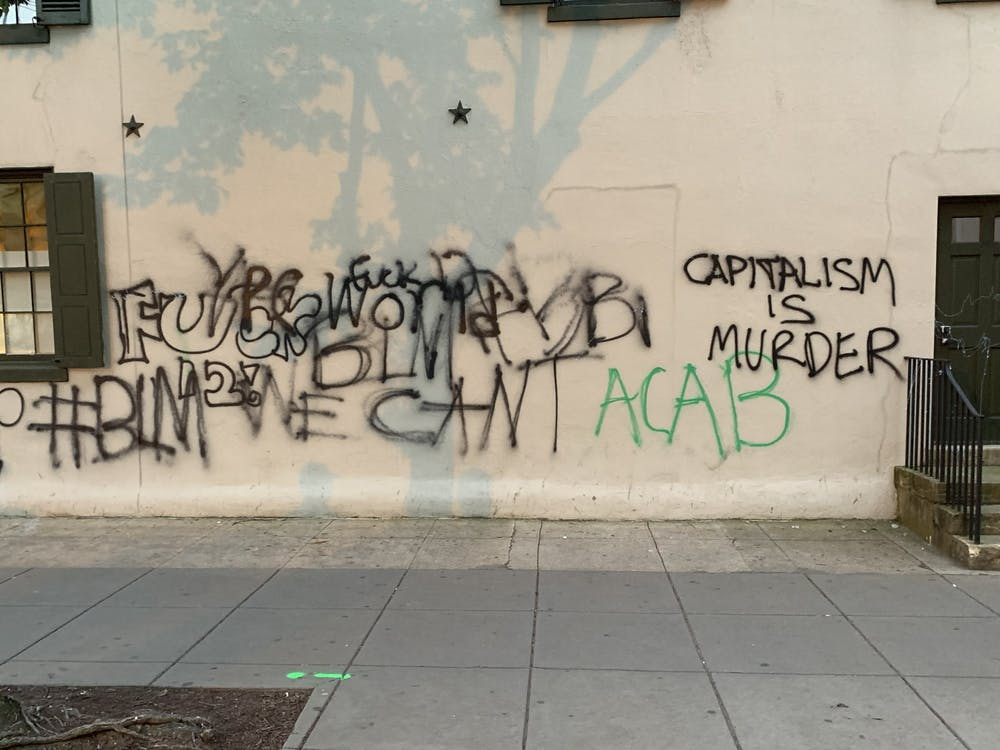 """Words and slogans such as """"capitalism is murder,"""" """"#BLM"""" and """"fuck 12"""" are spray painted on a wall in Washington, D.C."""