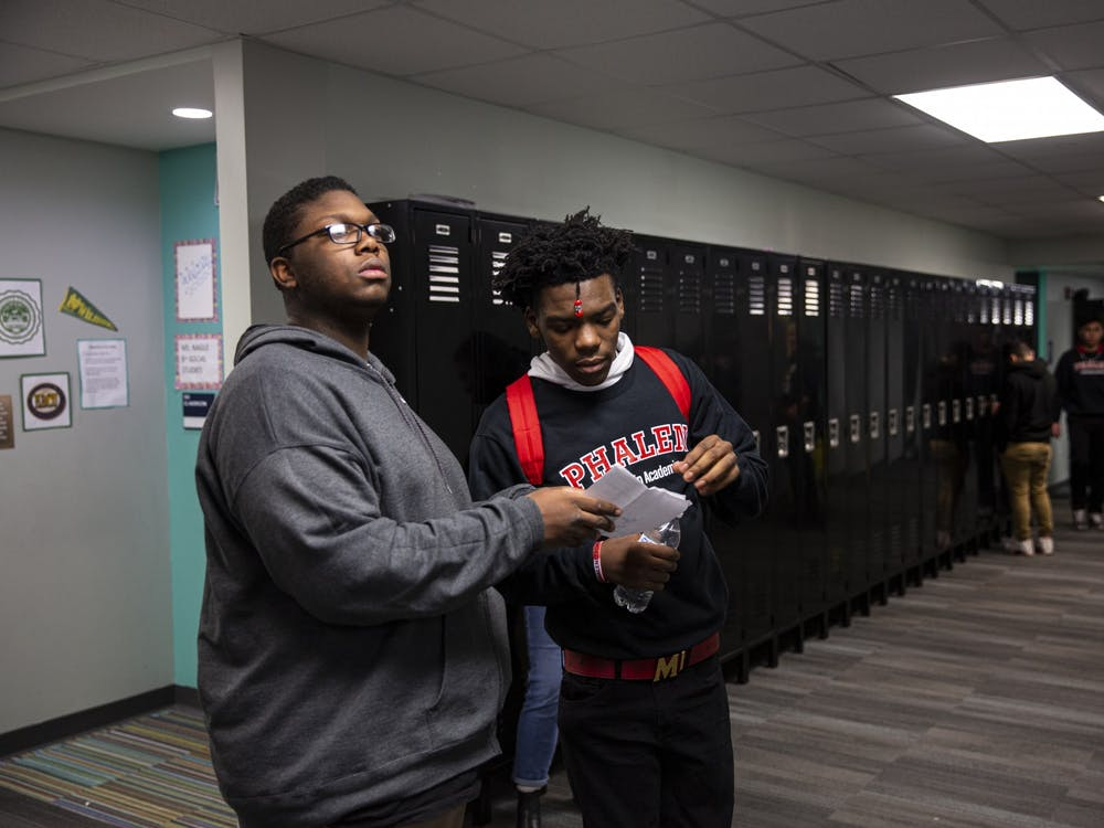 "Da'Quincy Pittman, right, and a classmate look at Pittman's schedule to find his first class of the day. Pittman doesn't always feel safe on the east side. ""You gotta watch over your shoulder,"" he said. ""You gotta watch who you're around."""