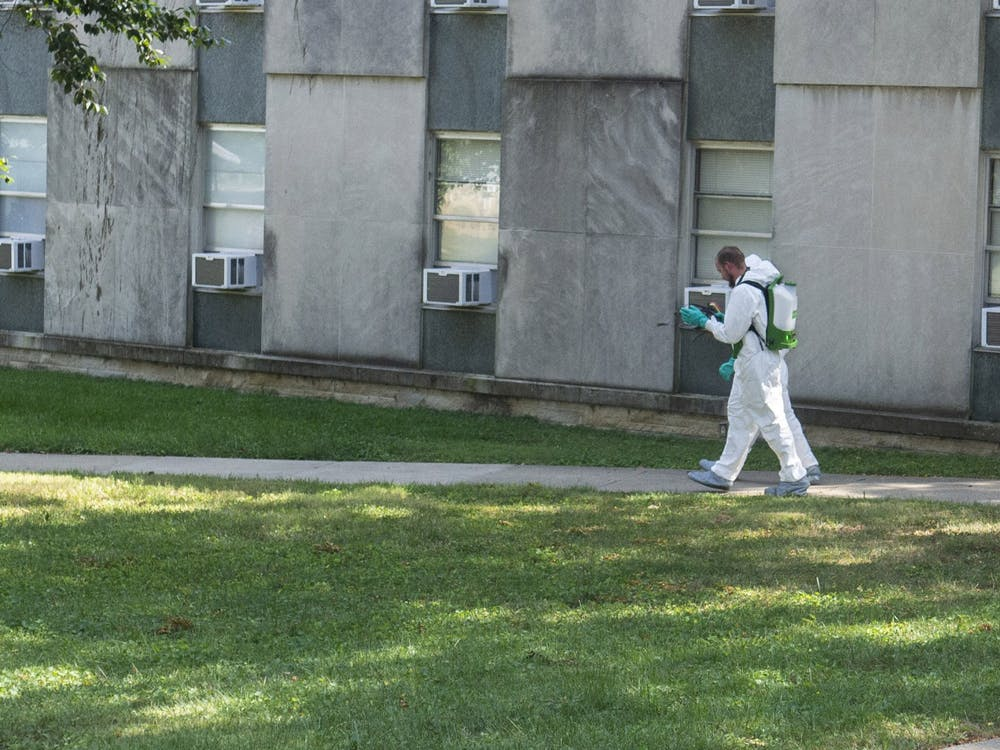 Two employees wearing protective gear walk between buildings Sept. 10 outside Ashton Residence Center. Employees that enter buildings or handle waste where COVID-19-positive residents are present wear protective gear.