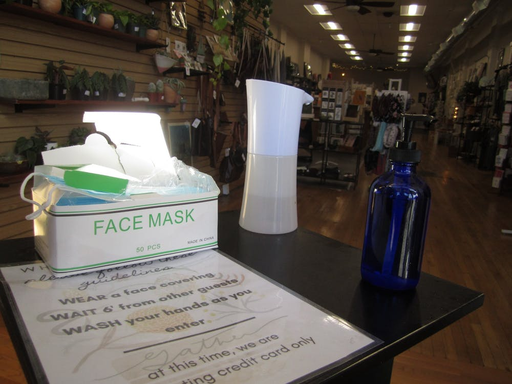 <p>Face masks and hand sanitizer sit on a table Thursday inside the entryway of Gather in order to promote health and safety among customers. Gather is located at 116 N. Walnut St. </p>