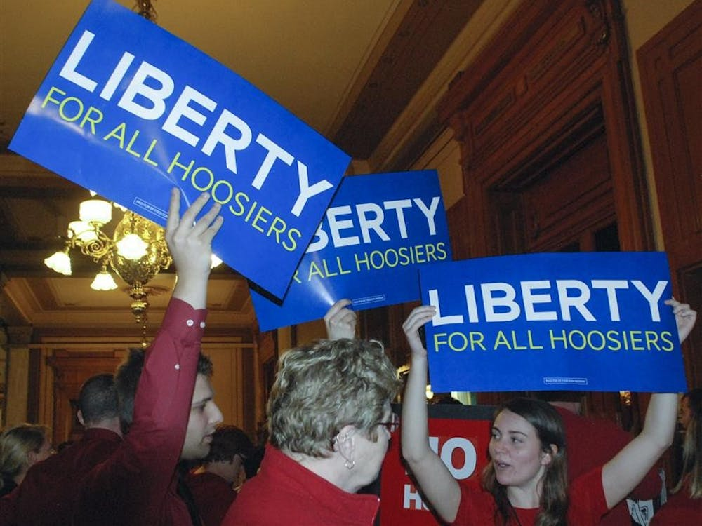 Freedom Indiana volunteers, including IU freshman and field organizer Morgan Mohr (far right), hold signs in the Statehouse on Monday. Inside the House of Representatives chamber, the Judiciary Committee was hearing testimony about House Joint Resolution 3, a constitutional amendment reaffirming the state's ban on same-sex marriage.