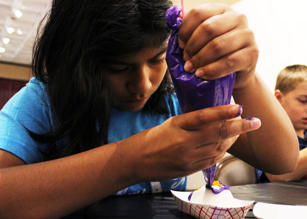 <p>Childs Elementary School student Karinna Kenner decorates a sugar skull Oct. 27 at the Mathers Museum of World Cultures. The museum celebrated Día de los Muertos with crafts and an altar in honor of dead loved ones. </p>