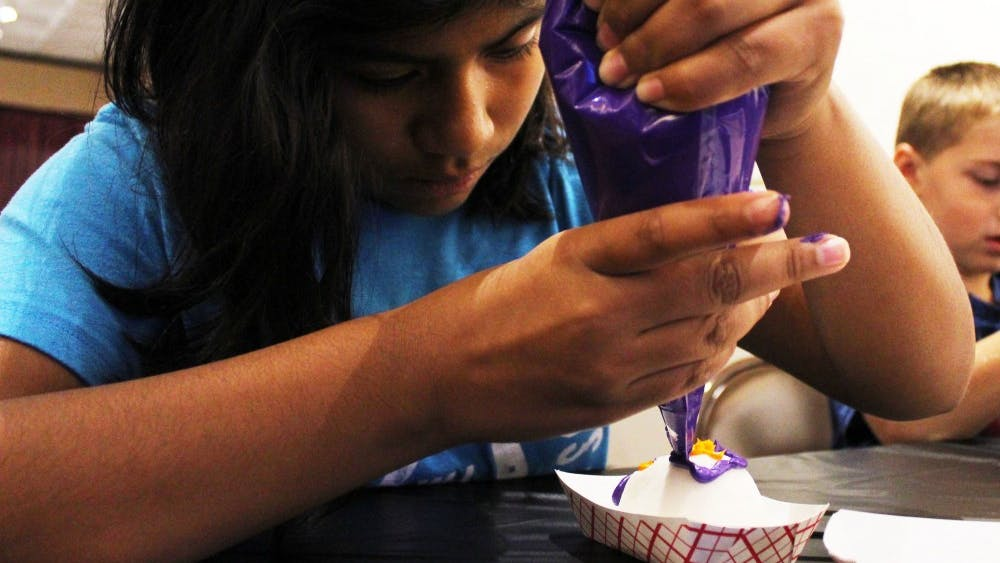 Childs Elementary School student Karinna Kenner decorates a sugar skull Oct. 27 at the Mathers Museum of World Cultures. The museum celebrated Día de los Muertos with crafts and an altar in honor of dead loved ones.