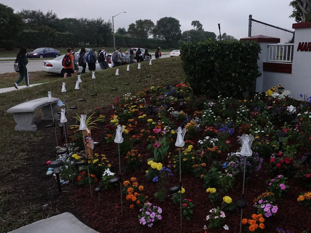 Students walk past the memorial garden outside of Marjory Stoneman Douglas High School in Parkland, Florida.