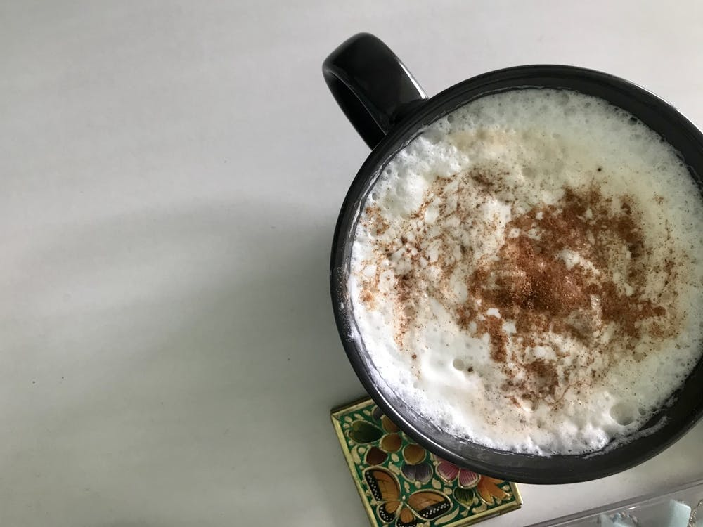A latte with cinnamon sprinkled on top is pictured on a table.