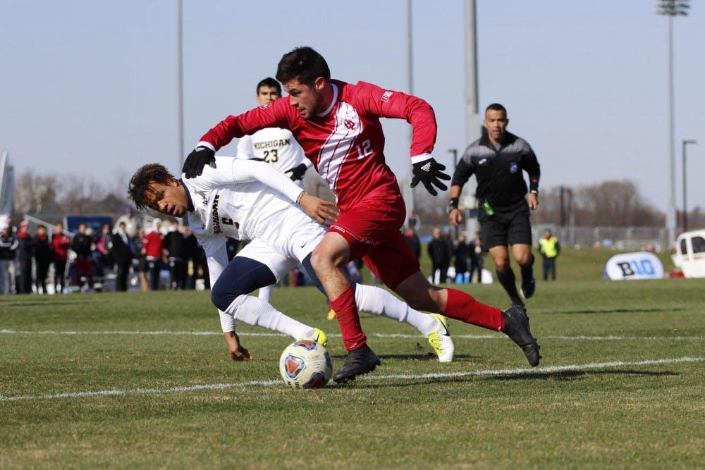<p>Senior midfielder Austin Panchot runs alongside a Michigan defender at the Big Ten Tournament Championship game Nov. 11 at Grand Park.</p>