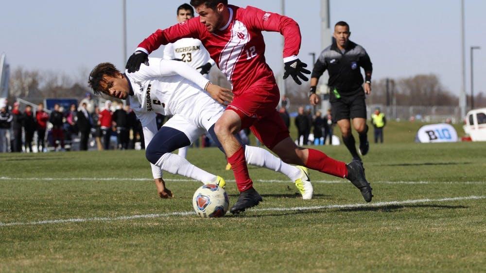 Senior midfielder Austin Panchot runs alongside a Michigan defender at the Big Ten Tournament Championship game Nov. 11 at Grand Park.