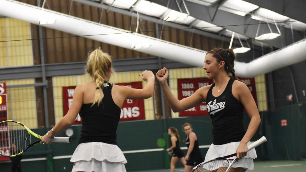 Junior Madison Appel and freshman Michelle McKamey celebrate after winning a point during their doubles match against University of Cincinnati. IU improved to 3-0 on the season after their 4-2 win over UC.