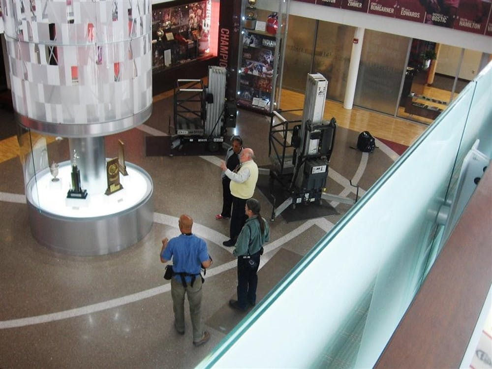 Bob Hammel talks with IU women's coach Felicia Legette-Jack in front of the bottom of the IU Tower, which features the 5 national championship trophies.