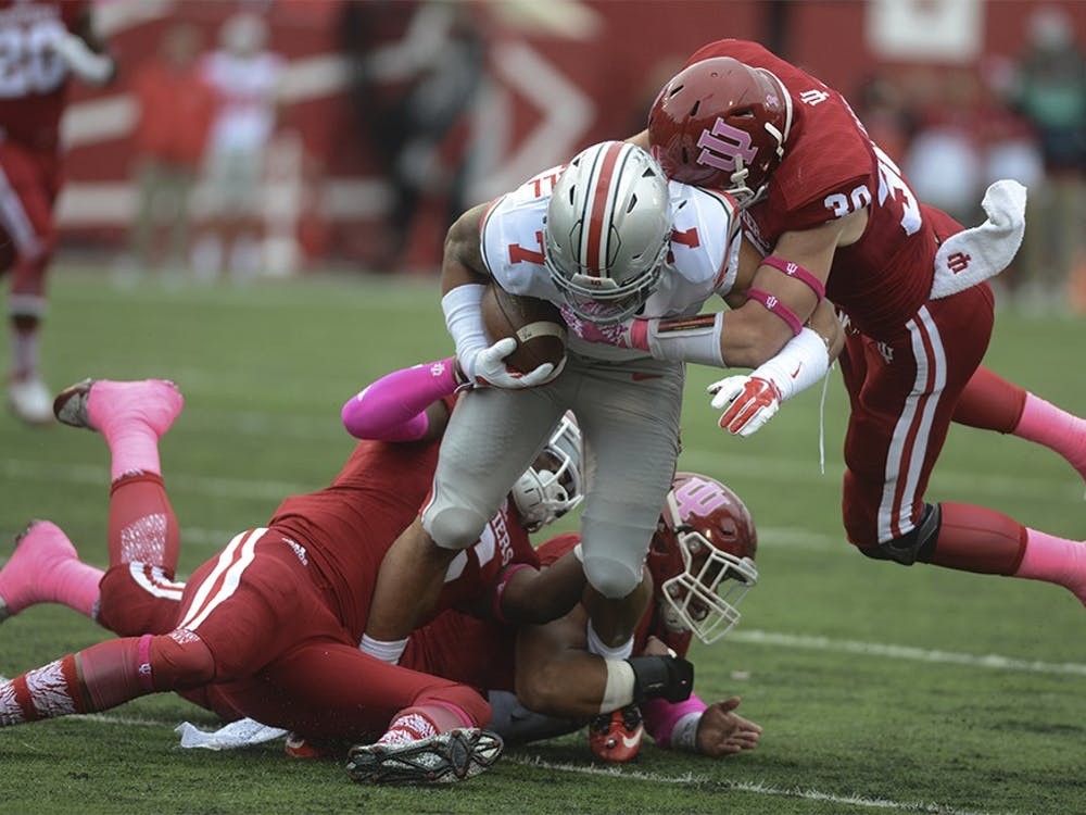 Linebacker Zeke Walker (6) and Oliver Marcus (44) and safety Chase Dutra (30) tackles Ohio State's Jalin Marshall (7) on Oct. 3 at Memorial Stadium. The Hoosiers lost to the number one ranked Buckeyes, 27-34.