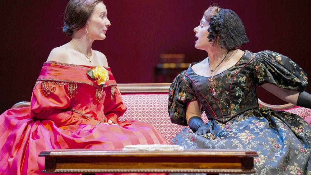"Catherine Sloper (left) and aunt Lavinia Penniman (right), portrayed by Glynnis Kunkel-Ruiz and Ellise Chase, socialize before a party during a rehearsal of Ruth and Augustus Goetz' ""The Heiress"" on Sept. 18 in Ruth N. Halls Theatre. The story focuses on Catherine Sloper, a wealthy, socially awkward woman, who falls in love with a man that her father believes is only after their money."