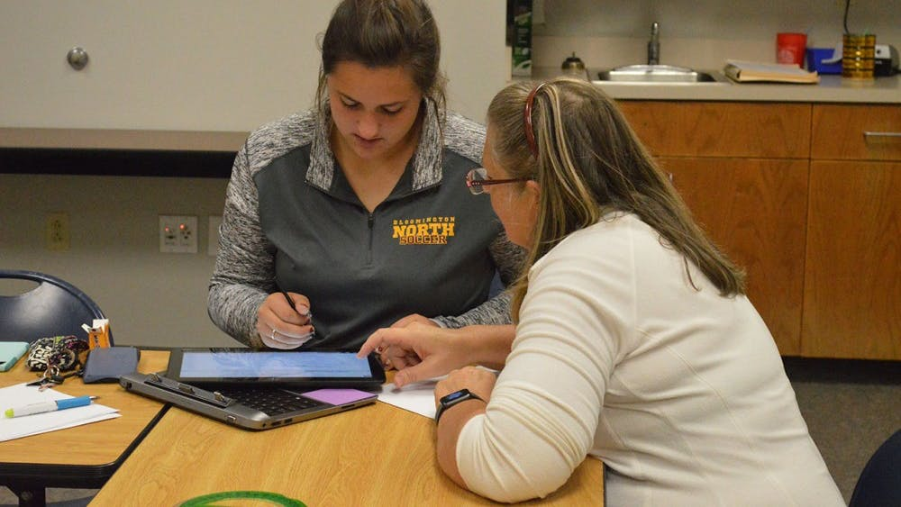 Jan Pierson, Lead Coordinator for Homework Help at Monroe County Library, helps Bailey Fries, 11th grader at Bloomington North High School with math homewok as part of the library's teen SAT prep sessions.