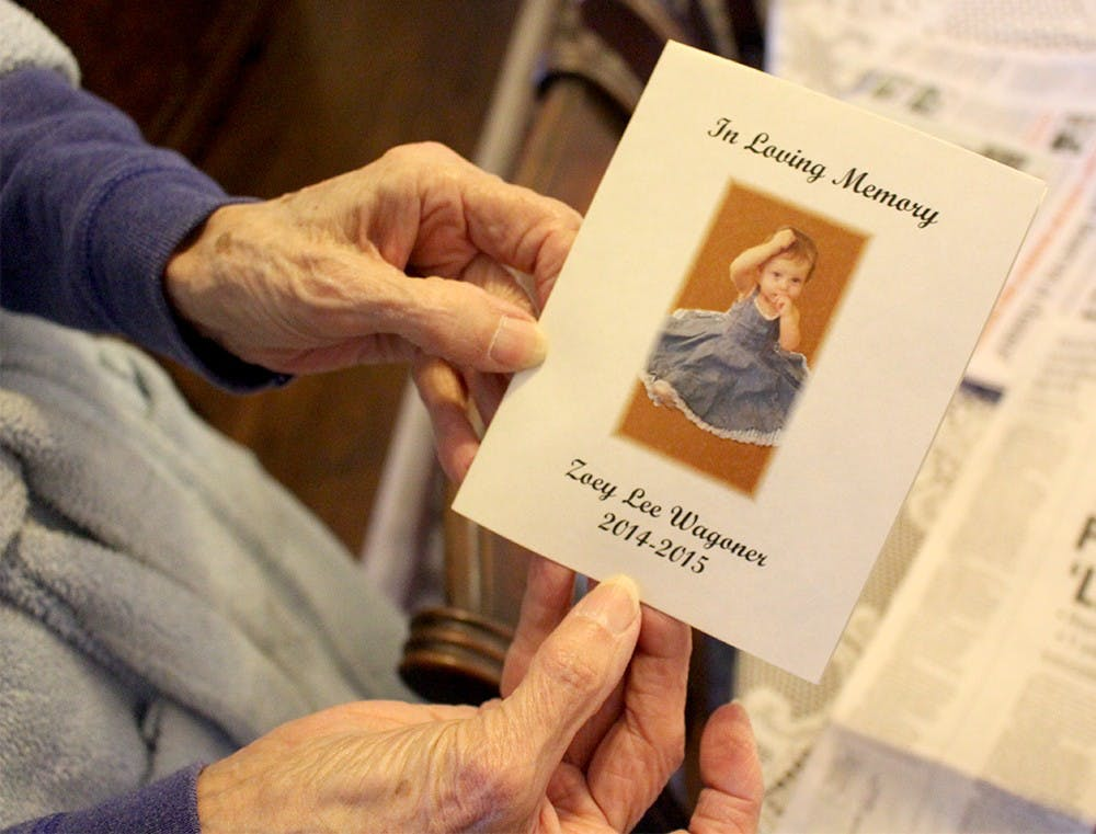 """Virginia McPherson, 85, the Wagoner's neighbor, holds the invitation she received last year to the funeral of one-year-old Zoey Wagoner Wednesday at her house. On Wednesday, the day of Matthew S. Wagoner's sentencing, she stayed inside her home in Greenfield with her dog Susie. Last May, on the day before Zoey was killed, she was sitting on her front porch with Susie when she saw Jessica Wagoner walking by in a stroller. Virginia went up and touched Zoey's hand and smiled at the infant. """"I'll never forget the look on that child's face,"""" she said."""