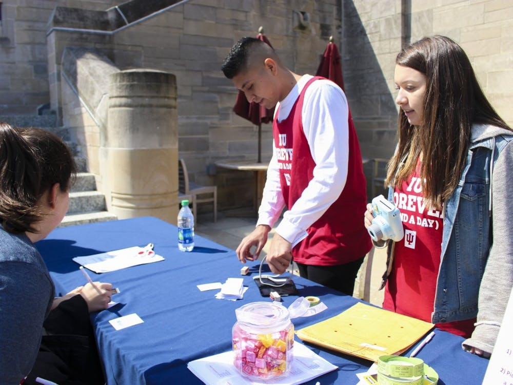 "Students Luis Gonzalez and Kayla Hardegre stamp students' scavenger hunt papers for IU Day in 2018 at a booth in front of the Indiana Memorial Union. Students could also get their pictures taken with a giant letter ""U."""
