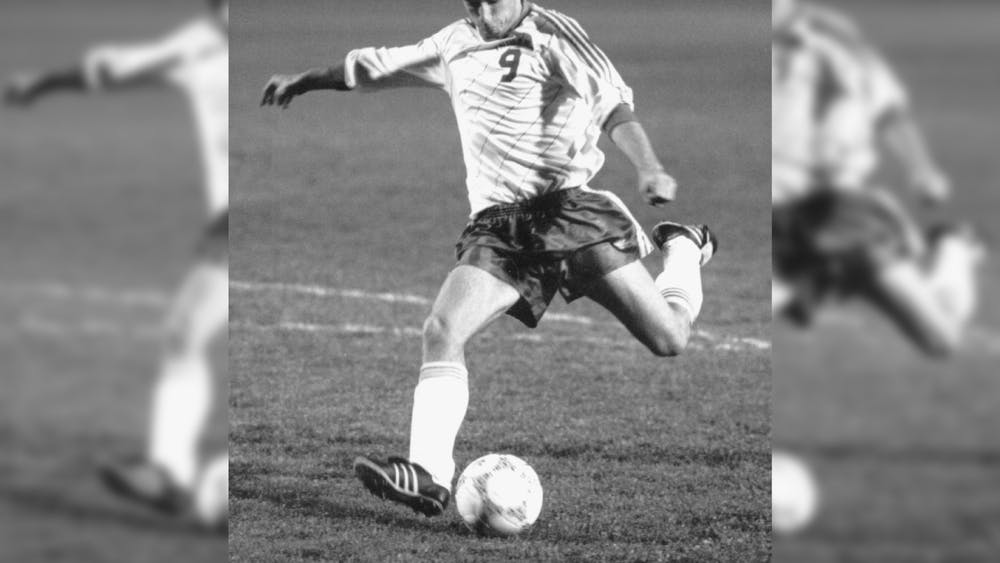 Men's soccer player Ken Snow kicks the ball during his time on the team from 1987-1990. Snow won a national title with the team in 1988.