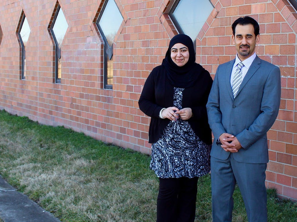 Faryal Khatri and Hazem Bata stand in front of the wall that was marred by anti Muslim graffiti over the weekend. A volunteer from the community scrubbed the wall clean the day of the incident.