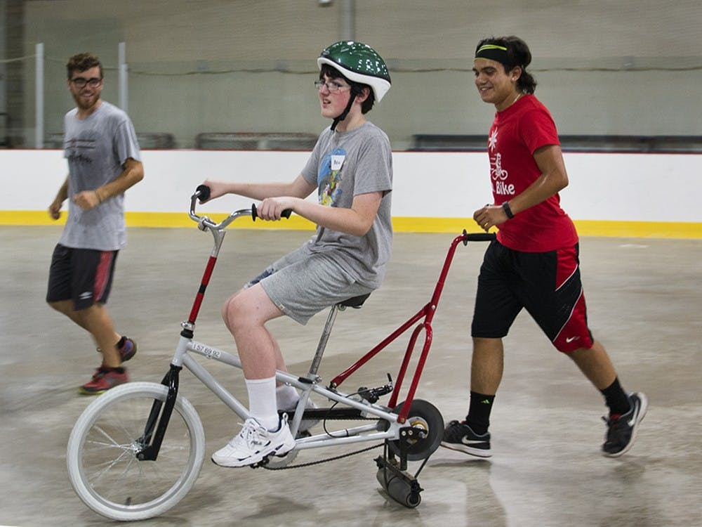 Quentin West, left, and Solustrisimo Jr. Garcia, assist Beau Jent, 12, riding the bike during the iCan Bike camp event held at Frank Southern Ice Arena on Monday evening. West said this is another good way to help this population that just want to be like everyone else.