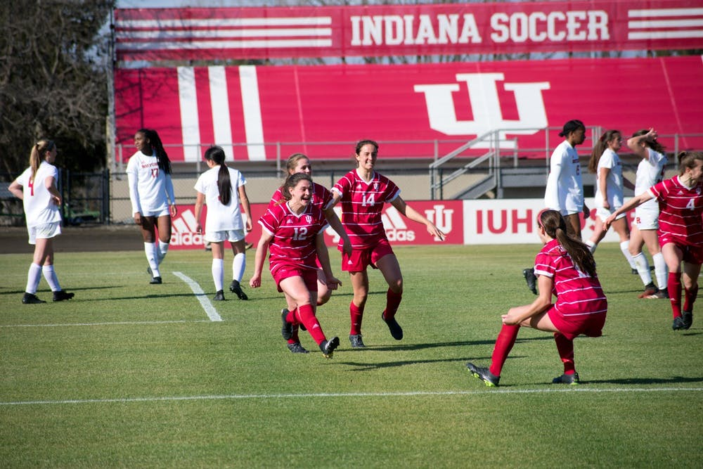 Players on the IU women's soccer team celebrate Feb. 25 during the game against Rutgers. IU tied Purdue 0-0 Saturday night in West Lafayette, Indiana.
