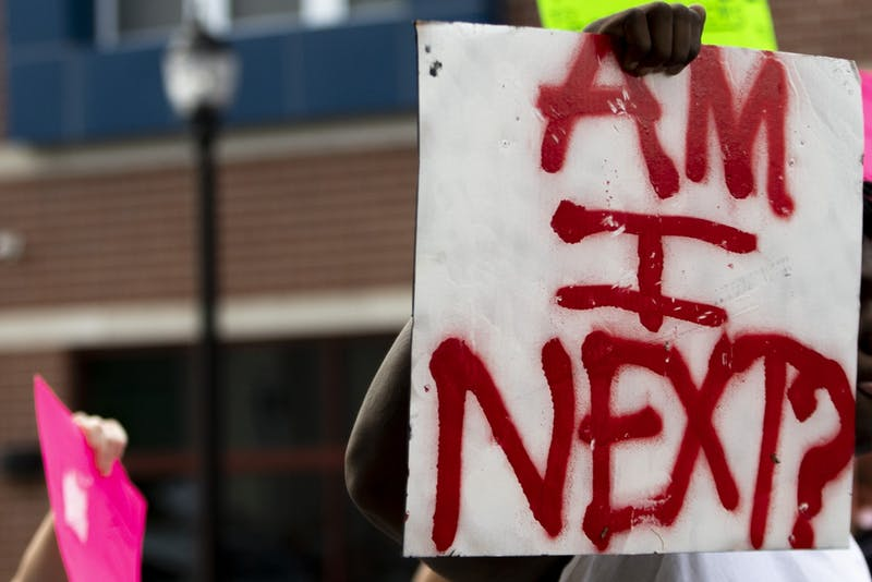A protester holds a sign June 1 on East Third Street. The protest went through the streets as traffic was blocked off.