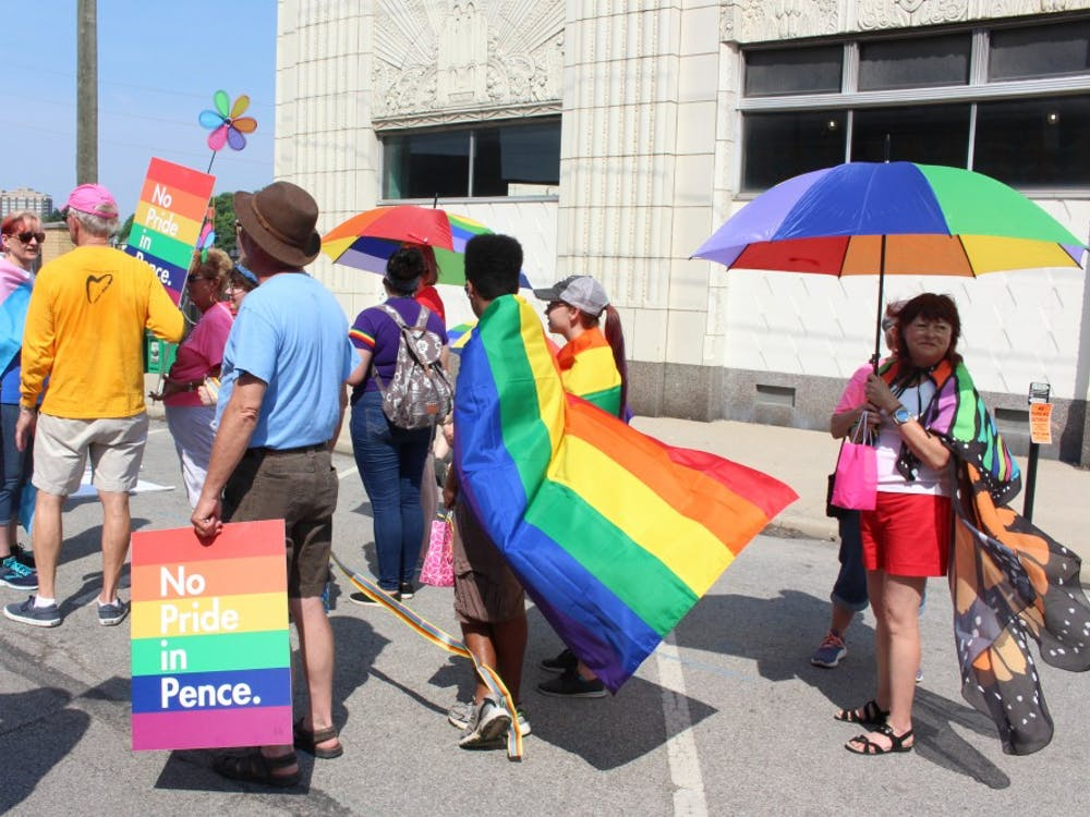 """A group walks while holding rainbow flags, umbrellas and signs that say, """"No Pride in Pence"""" at the Indy Pride Festival. The festival took place on Saturday, June 9, in Indianapolis."""