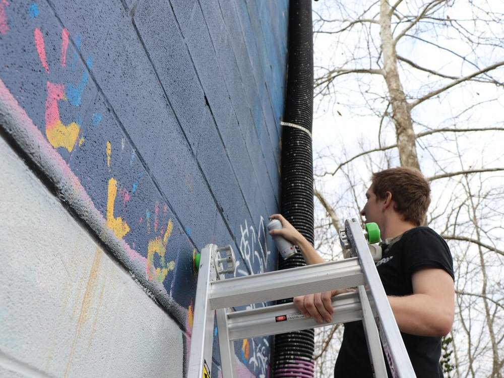 Sophomore Trenton Musch works on a mural Nov. 20 outside of The Warehousein Bloomington. Musch is a comprehensive design major.