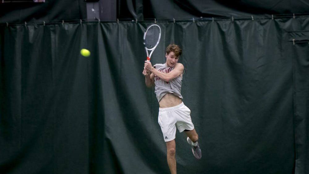 IU senior Bennett Crane leaps for the ball in a match against the University of Memphis Jan. 17 at the IU Tennis Center.  IU will play the University of Texas at Austin on Saturday in Austin, Texas.