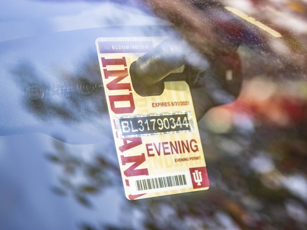 An evening parking permit hangs from the rearview mirror of a car in Bloomington. Evening permits are one of several different kinds of permits issued for on-campus parking.