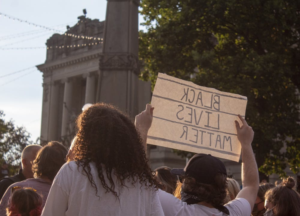 "<p>A man holds a sign reading ""Black Lives Matter"" at a counter-protest to the Red, White and Blue rally members Aug. 22 on the corner of Kirkwood Avenue. Near halfway into the event the protesters were shouting across Walnut Avenue to counter-protesters.</p>"