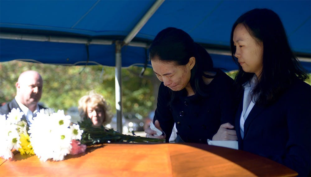 Yan Li, Yaolin Wang's cousin, holds Jielin Wang, Wang's sister, in front of Yaolin's casket before it went underground during the burial service on Oct.11.  Jielin was the last one to leave after the casket was in the ground.