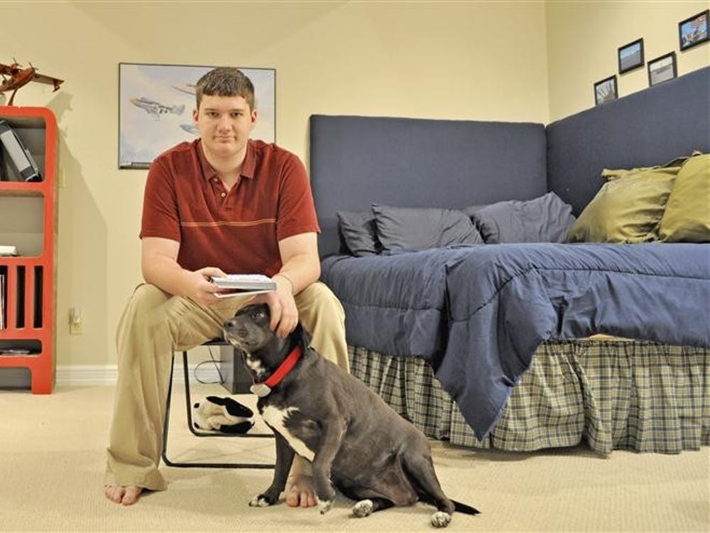 Kameron Breedlove pets his dog JC, in his newly renovated room which has furniture arranged and colored to recharge and stimulate his senses. The blue bedcovers have a relaxing effect and red colored study area helps increase concentration.