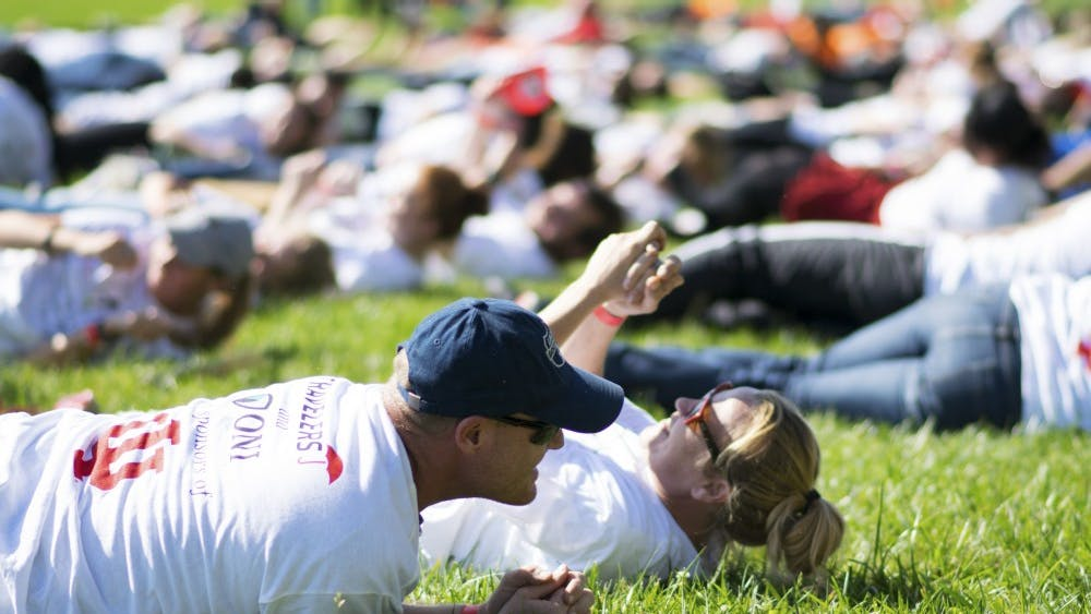 IU employees Herb Jones and April Purlee roll on the ground as part of the Office of Insurance, Loss Control & Claims' organized attempt to break the current world record of 1,719 people simultaneously stop, drop and rolling. The Guinness World Records requires participants roll on the ground for 30 seconds in order for the attempt to count.