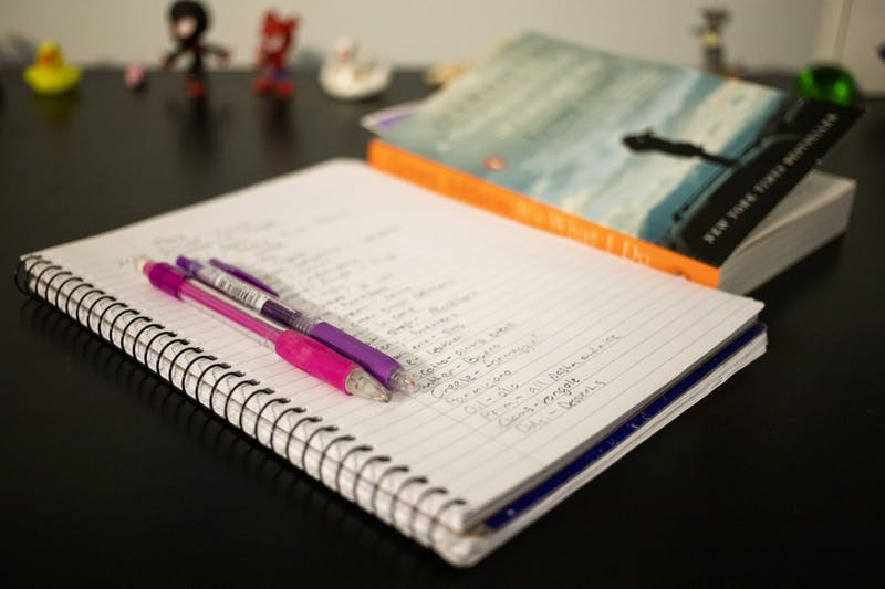 A notebook and book sit on a desk.
