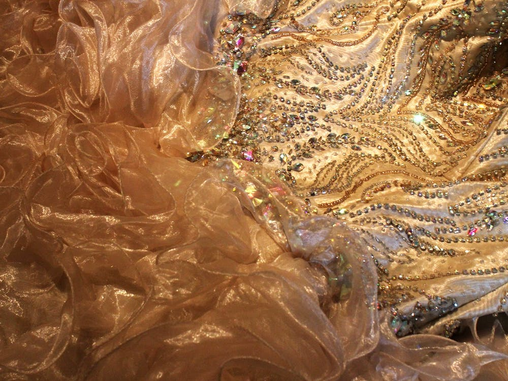 Backstage, a quinceañera gown rests on the floor Sept. 26 while models prepare for the runway for  the15th annual Fiesta de Otoño on Kirkwood Avenue. The dress is beige and decorated with colorful gemstones.
