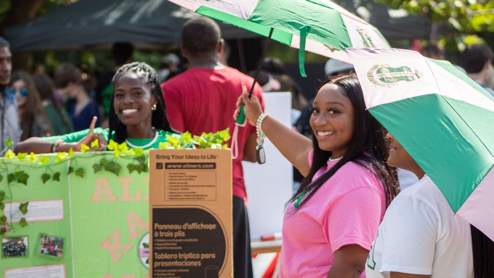 IU seniors Lorraine Michira, left, and Zianne Thomas, right, hold up umbrellas while representing the Tau Chapter of Alpha Kappa Alpha, Incorporated, at the Involvement Fair Aug. 26, 2021, in Dunn Meadow. The Involvement Fair was held virtually last school year.