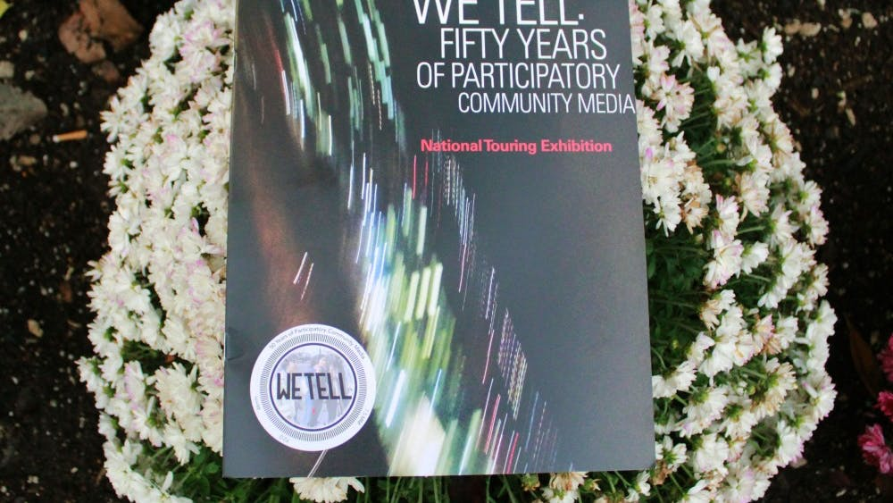 """A booklet sits on a flower bed on Oct. 21 in front of the IU Cinema. """"We Tell: Body Publics"""" is part of the traveling national exhibit, """"We Tell: Fifty Years of Participatory Community Media,"""" and showed several short films."""