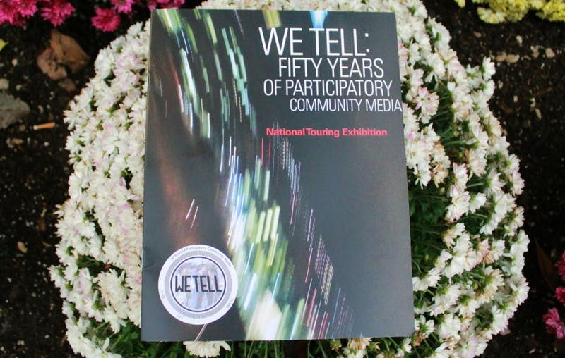 "A booklet sits on a flower bed on Oct. 21 in front of the IU Cinema. ""We Tell: Body Publics"" is part of the traveling national exhibit, ""We Tell: Fifty Years of Participatory Community Media,"" and showed several short films."