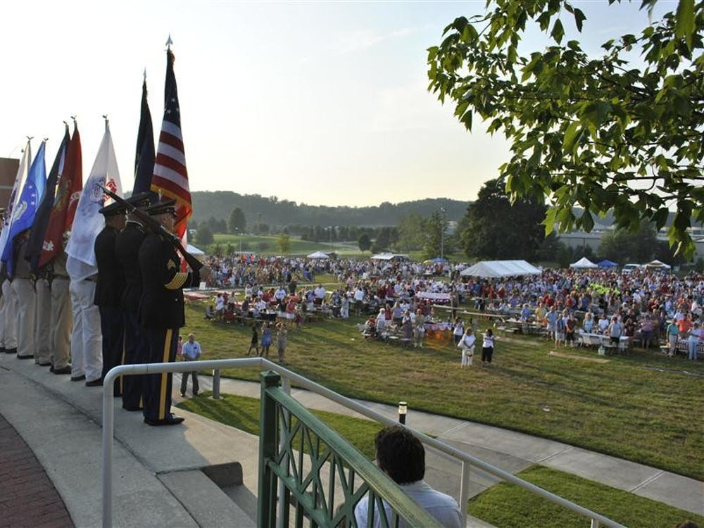 The crowd watches as the color guard brings flags to the stage.