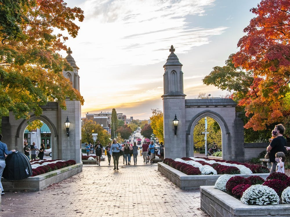 People walk by Sample Gates at sunset Oct. 12. A group of students began a petition Nov. 6, asking for IU to allow the option of satisfactory and unsatisfactory grading for all IU classes for both the fall 2020 and spring 2021 semesters.