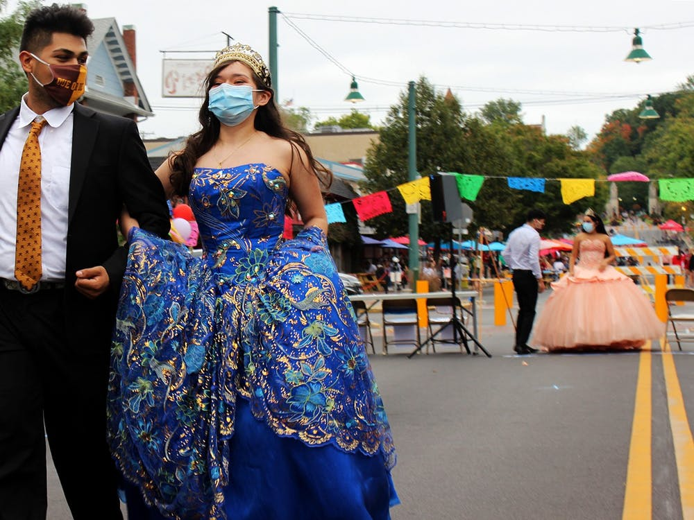 IU students Lalo Vera and Karen Rodriguez walk down the road Sept. 26 on Kirkwood Avenue. Rodriguez models her gown and tiara from her quinceañera.
