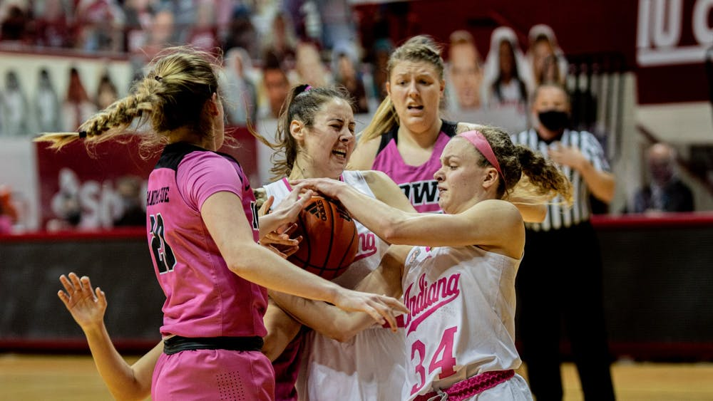 Sophomore forward Mackenzie Holmes and junior guard Grace Berger wrestle for the ball against Iowa on March 3 at Simon Skjodt Assembly Hall. Holmes and Berger were among four IU women's basketball players to receive All-Big Ten Honors awards Monday.