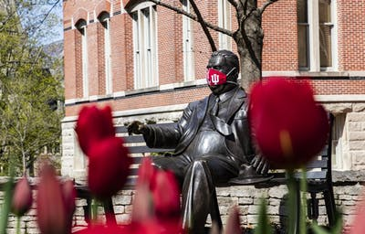 A face mask covers the face of the Herman B. Wells statue April 20 on IU's campus. IU released more specific information about how the university will handle COVID-19 issues this fall in a July 30 webinar.