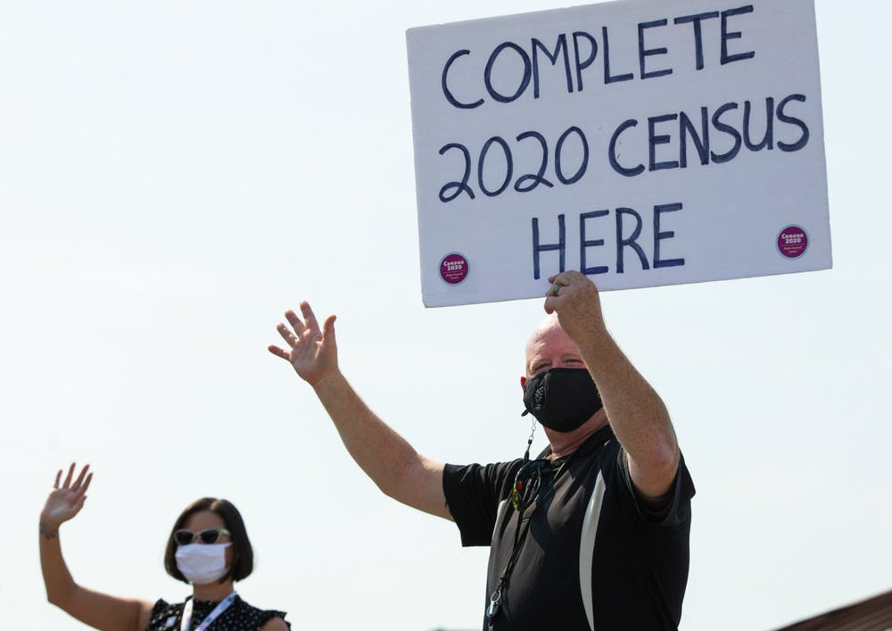 <p>D.J. Fox, right, holds a sign encouraging people to complete the 2020 census and waves to passersby Sept. 4, in Des Moines, Iowa. </p>