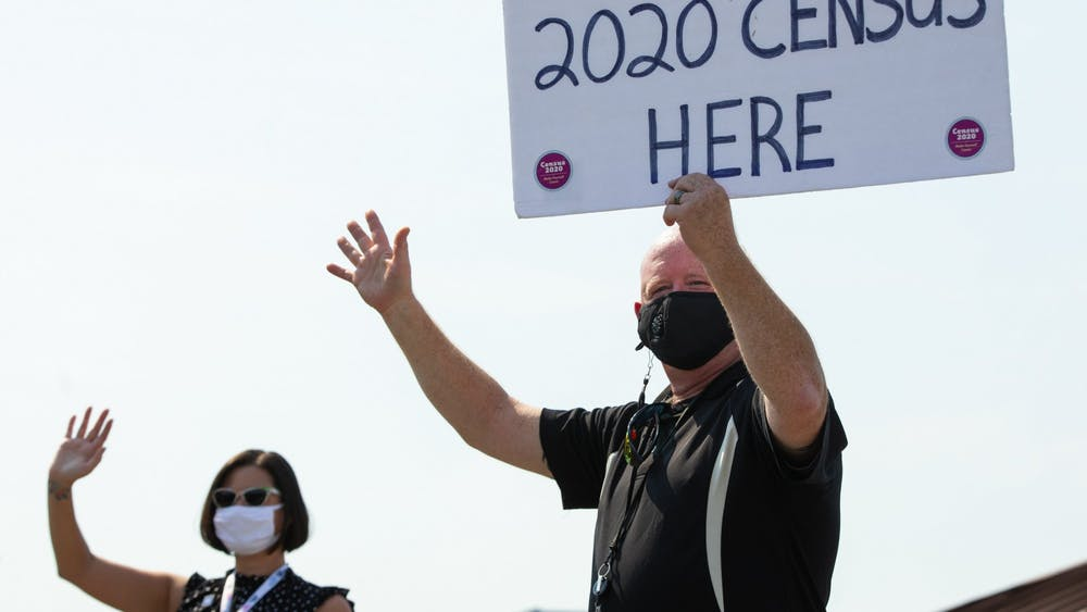 D.J. Fox, right, holds a sign encouraging people to complete the 2020 census and waves to passersby Sept. 4, in Des Moines, Iowa.