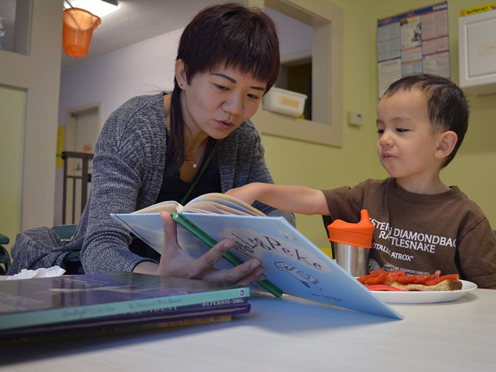 """Xinrui Song reads """"Peg Leg Peke"""" to son Sven Weitnauer while he eats breakfast at Knee High Cooperative Daycare Friday morning. Song has taken her two sons to Knee High four and a half years."""
