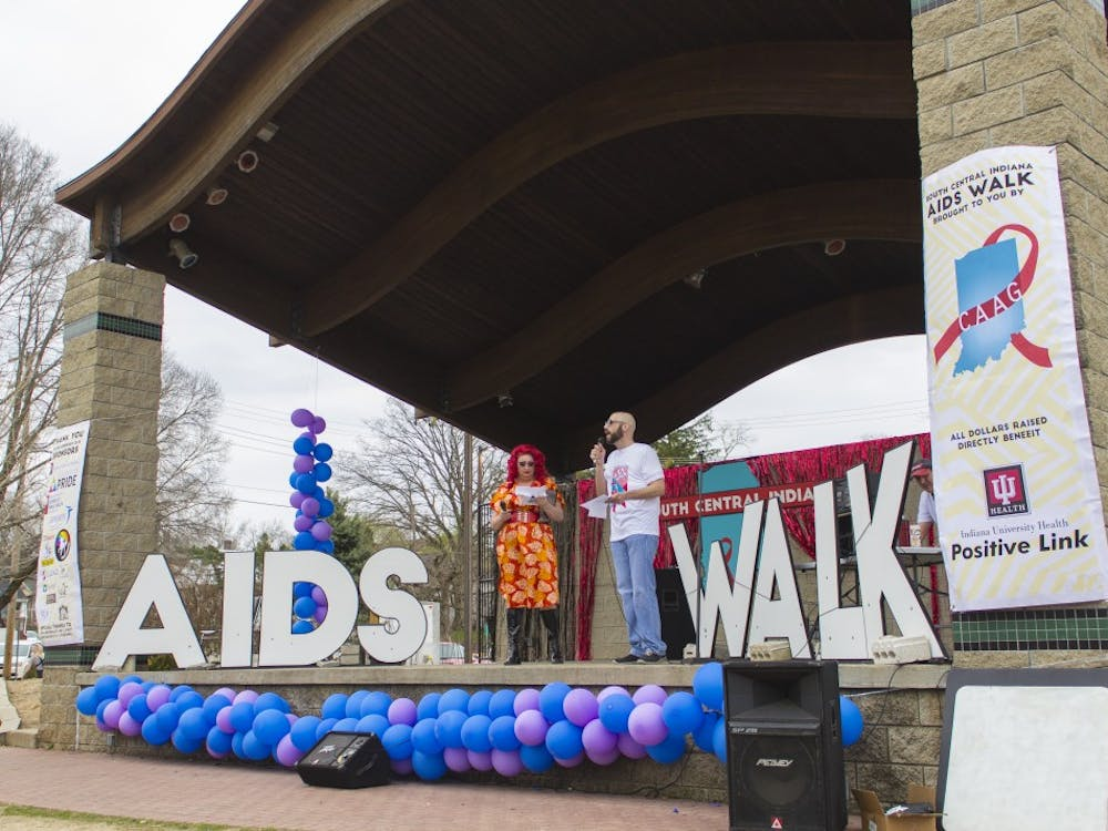 Argenta Peron and Jeremy Turner introduce the South Central Indiana AIDS Walk with opening remarks Friday at the Waldron Hill Buskirk Park. Peron flew in from Hawaii to participate in the event to raise awareness in the fight against AIDS.