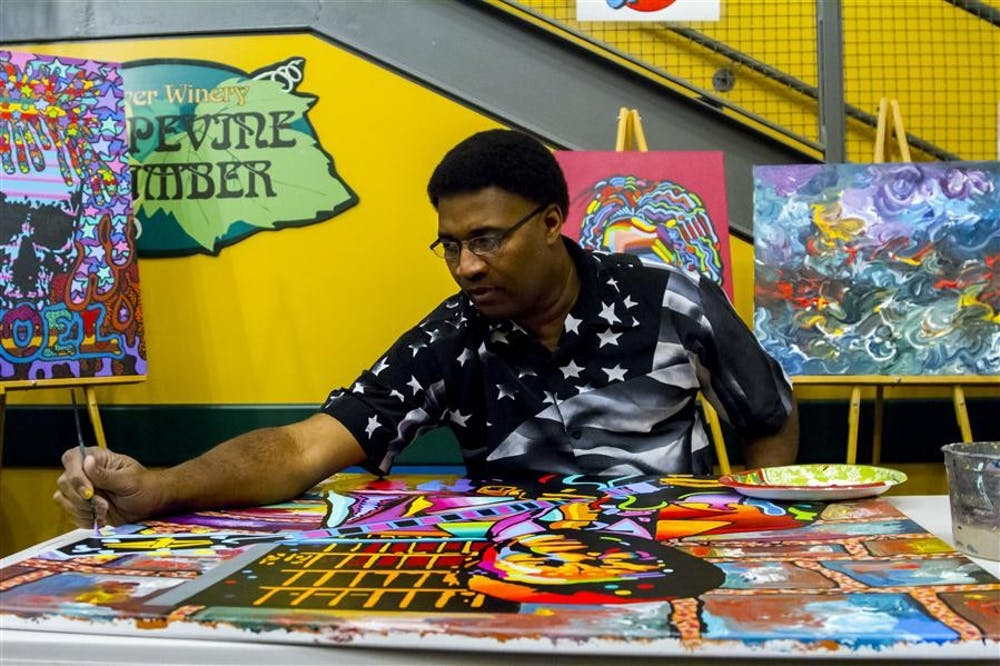 Local artist Joel Washington paints a colorful portrait of B. B. King on Friday evening at the WonderLab Museum of Health, Science and Technology. Children watched him work as part of the First Friday Evening Science of Art sponsored by the museum.